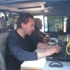 De reporter die op pad is, bereidt zijn stuk voor in de auto.