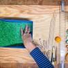 <p>Knip een rechthoek uit een groen papier en plak het op de bodem van de doos. </p>