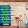 <p>Knijp de wasknijpers op de stokjes. Zorg ervoor dat de kleuren kloppen (zie foto).</p>