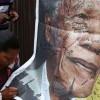 Zuid-Afrikanen schrijven een tekst op een poster van Mandela